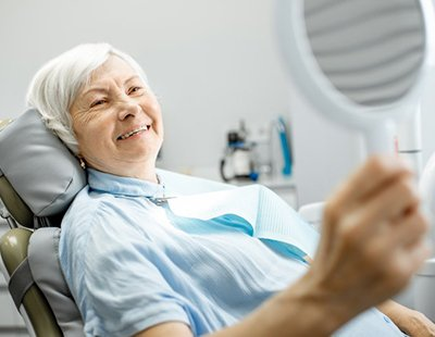 older lady sitting in dental chair and smiling into hand mirror after dental bonding treatment