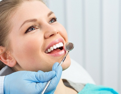 A young woman smiling with her mouth open while a dentist prepares to examine her smile