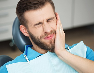 Man holding cheek during emergency dentistry appointment